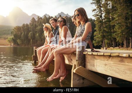 Portrait de groupe de jeunes gens assis sur le bord d'une jetée, à l'extérieur dans la nature. Les amis passer une Banque D'Images