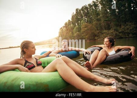 Portrait de jeunes amis flottant sur le lac avec anneaux gonflables. Les jeunes se détendre dans l'eau un jour d'été. Banque D'Images