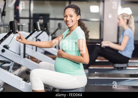 Femme enceinte l'exercice et à la recherche à l'appareil photo