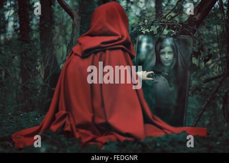 Femme à capuche rouge mystérieux en face d'un miroir magique. Dark fantasy Banque D'Images