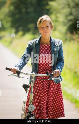 Pensive woman poussant son vélo Banque D'Images