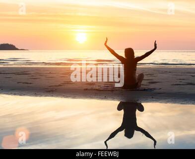 Silhouette of woman doing Yoga exercice au coucher du soleil sur la plage avec reflet dans l'eau. Banque D'Images