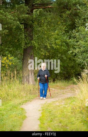 Une femme âgée sur une promenade dans le parc la pratique de la marche nordique. Banque D'Images