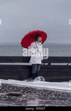 Une femme en blouse blanche avec un parapluie rouge à la mer en hiver