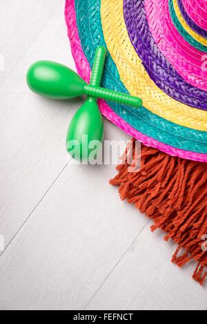 Sombrero mexicain, couverture et paire de maracas sur fond de bois.