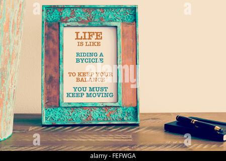 Effet rétro et d'une image aux couleurs vintage photo frame avec citation de motivation à côté de l'ordinateur portable Banque D'Images