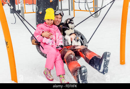 Homme assis sur la balançoire avec husky puppy dog et sa fille en hiver Banque D'Images