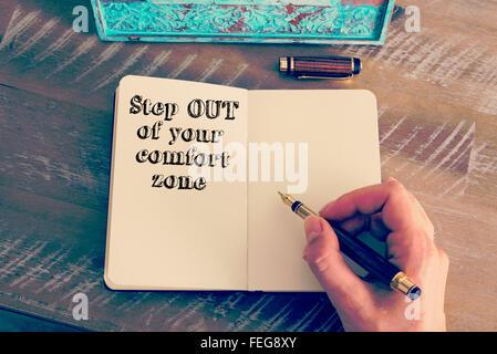 Effet rétro aux couleurs et image d'une femme d'écrire une note à la main avec un stylo sur un ordinateur portable.