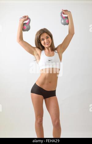 Jeune femme avec corps mince holding up électrique cloches et à happy Banque D'Images