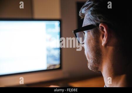 Jeune homme poils concentrés dans les verres assis et à la recherche d'écran à surveiller Banque D'Images