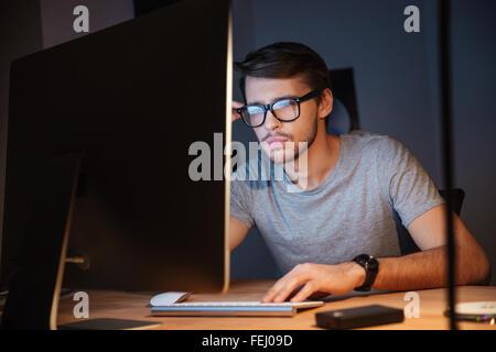 Jeune homme sérieux dans les verres réfléchir et travailler avec l'ordinateur dans une pièce sombre