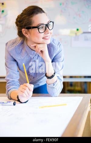 Inspiré belle jeune femme d'affaires dans les verres working in office Banque D'Images