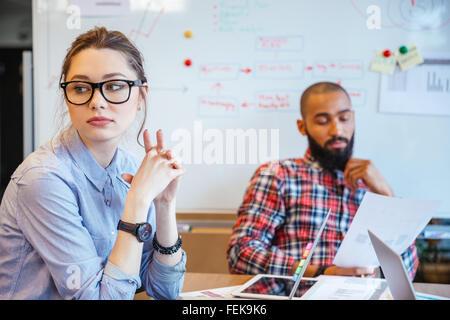 Pensive young woman in glasses assis dans la salle de conférence et de penser alors que son collègue masculin lecture Banque D'Images