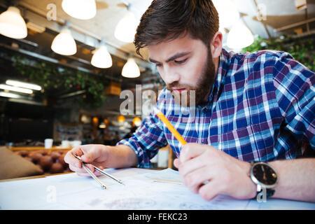 Jeune homme ingénieur travaillant sur blueprint in office Banque D'Images