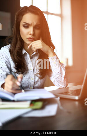 Directeur financier en prenant des notes quand on travaille sur le rapport Banque D'Images