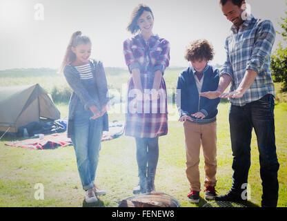 Réchauffement de la famille les mains au feu de camp Banque D'Images