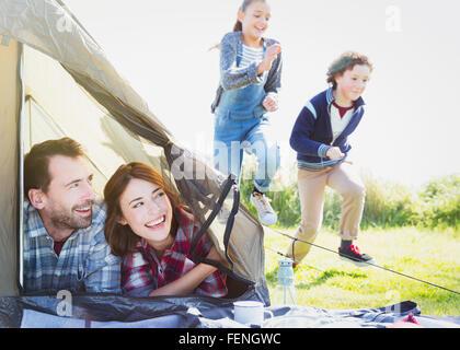 Smiling couple tente en regardant des enfants qui courent dans l'herbe Banque D'Images