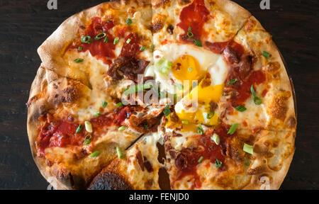 Pizza, petit déjeuner avec bacon, saucisses, tomates, mozzarella et deux œufs au plat Banque D'Images