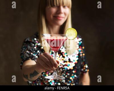 Mid adult woman holding jus cru dans verre à cocktail garni d'une tranche de lime smiling at camera