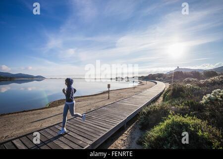 Jeune coureuse d'exécution sur Beach Boardwalk, Villasimius, Sardaigne, Italie Banque D'Images