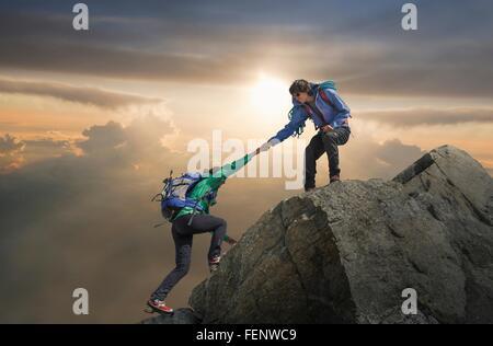 Partenaire aidant grimpeur atteindre sommet de montagne, Mont Blanc, France Banque D'Images