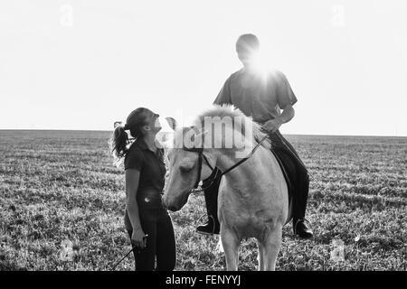 B&W image de la femme chat avec l'homme à cheval gris cheval dans le champ