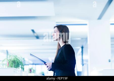 Vue latérale du young woman in office service representative, holding digital tablet looking away Banque D'Images