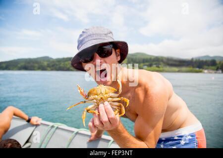 Portrait of mid adult man holding crab sur bateau de pêche, Nehalem Bay, Oregon, USA Banque D'Images