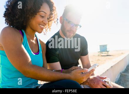 Couple sitting on wall looking at smartphone Banque D'Images