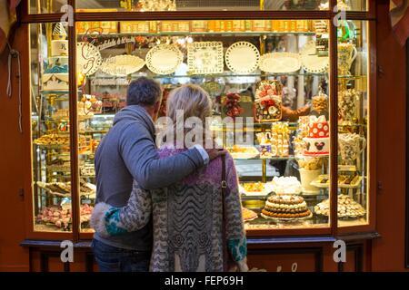 Vue arrière du couple romantique à cake shop window, Majorque, Espagne Banque D'Images
