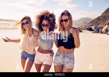 Portrait de trois jeunes femmes amis marchant sur le bord de la mer à la caméra à rire. Les jeunes femmes multiraciales Banque D'Images