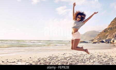 Portrait de belle jeune femme sautant dans l'air à la plage. Femme africaine à profiter d'une journée d'été au bord de la mer.