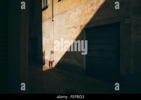 Boy leaning against wall en plein soleil looking at camera Banque D'Images