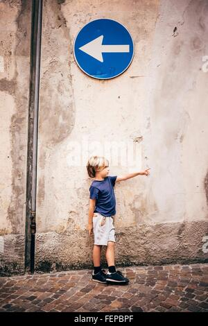 Boy leaning against wall sous direction sign pointing Banque D'Images