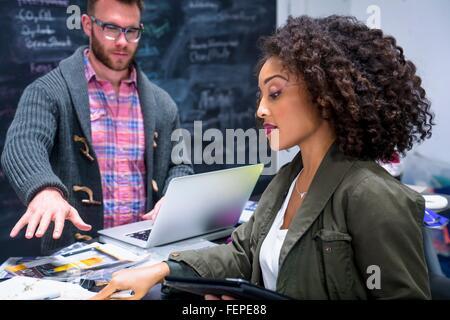 Collègues de travail en utilisant un ordinateur portable et tablette numérique Banque D'Images