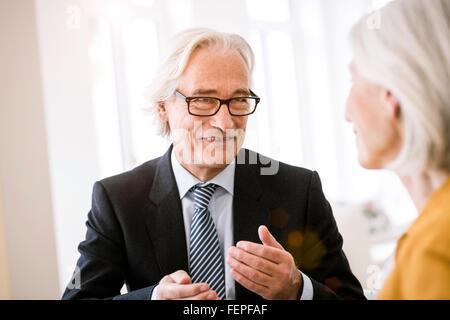 Hauts homme portant chemise, cravate et veste de costume de parler à senior woman Banque D'Images