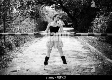 Une belle jeune blonde ballerine est debout sur ses orteils en face d'une porte de la rampe.Cette photo est en noir Banque D'Images
