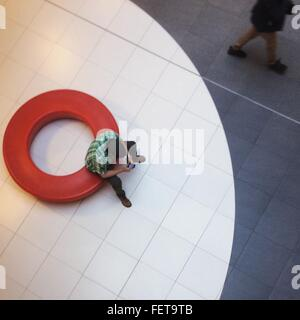 High Angle View Of Man Using Mobile Phone In Lobby Banque D'Images