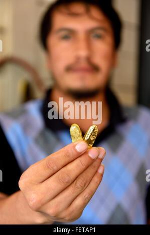 Homme tenant deux pièces d'or en boutique, ville minière de Laberinto, Puerto Maldonado, Madre de Dios, Pérou Banque D'Images