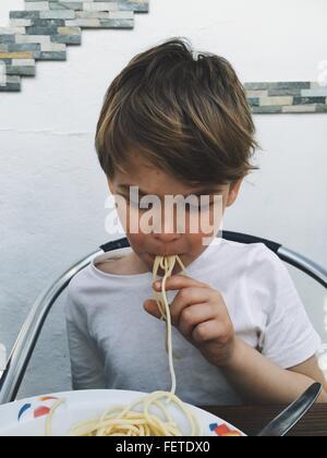 Boy Eating Spaghetti à la maison Banque D'Images