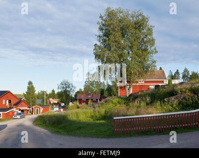 JUNGFRUKUSTEN, Suède le 17 juillet 2012. Avis de plusieurs bâtiments rouge allumé en soirée. Route de gravier, clôture Banque D'Images