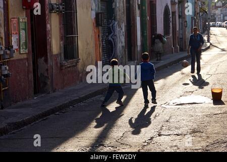 Frères jouant au football dans la rue avec leur mère. Banque D'Images