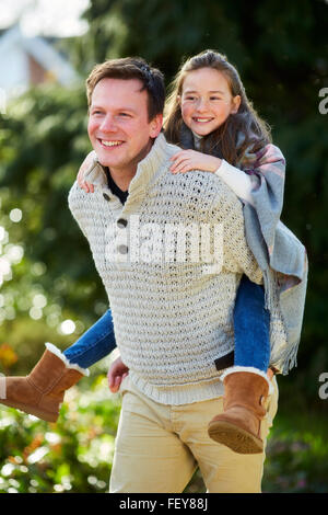 Father giving daughter piggyback Banque D'Images