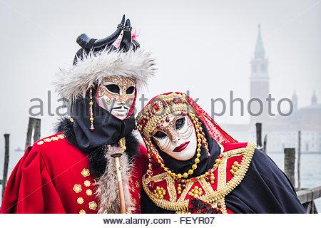 Venise, Italie - 02 février 2016: Couple en rouge costumes et des masques poser pour les photographes au Carnaval Banque D'Images
