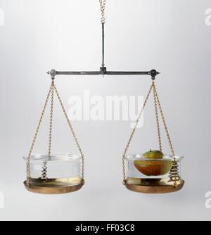 Plateau de balance avec un bol d'eau et un bol contenant une pomme sur elle, illustrant le principe d'Archimède Banque D'Images