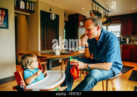Nourrir bébé père fils dans une chaise haute Banque D'Images