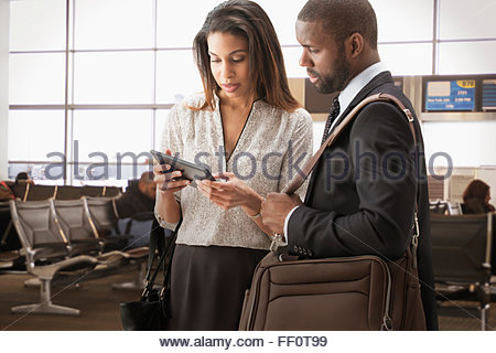Business people using digital tablet in airport Banque D'Images