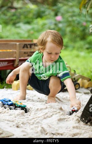 Un jeune garçon joue avec les camions dans un bac à sable à l'extérieur. Banque D'Images
