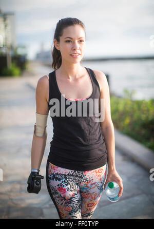 Mixed Race athlète amputé marche sur urban waterfront