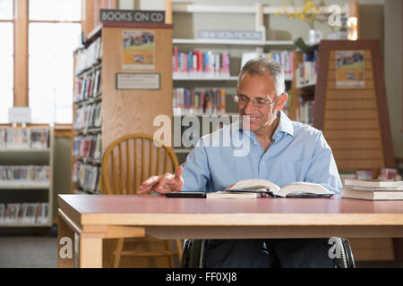 Caucasian man reading in library Banque D'Images
